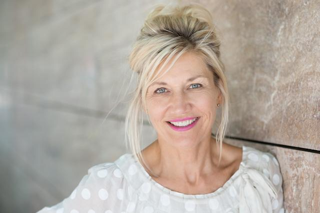 A woman smiles, leaning against a wall | Dental Extractions in Colorado Springs CO