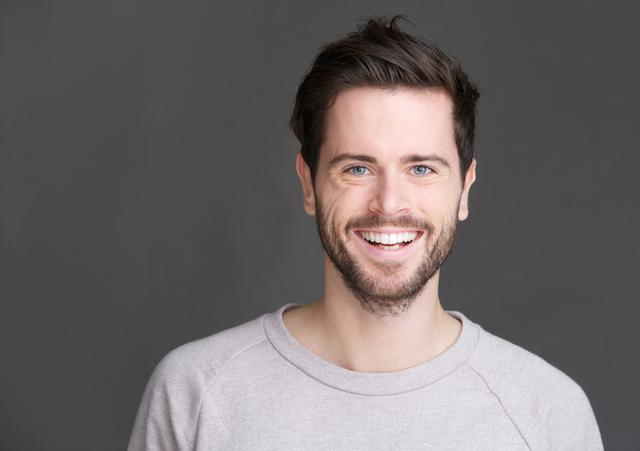 A man smiles infront of a grey background | Colorado Springs CO Dental Fillings