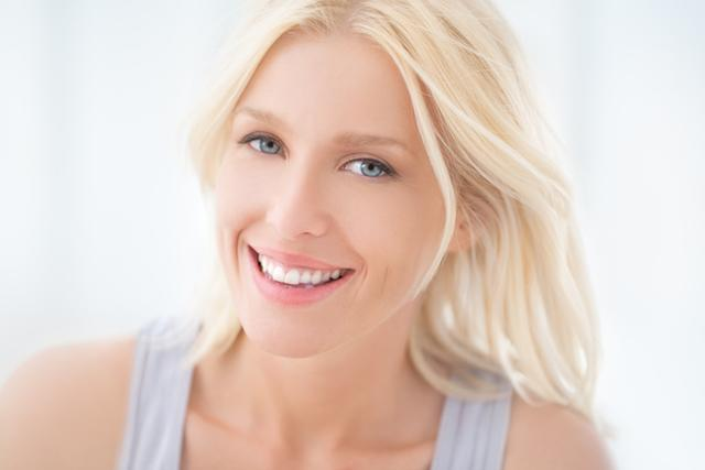 A woman smiles in front of a white backdrop | Cosmetic Bonding in Colorado Springs CO
