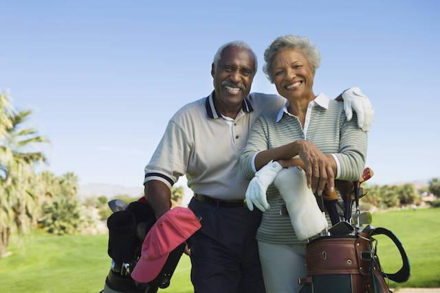 An older couple smiles on the golf course | Periodontal disease treatment colorado springs co