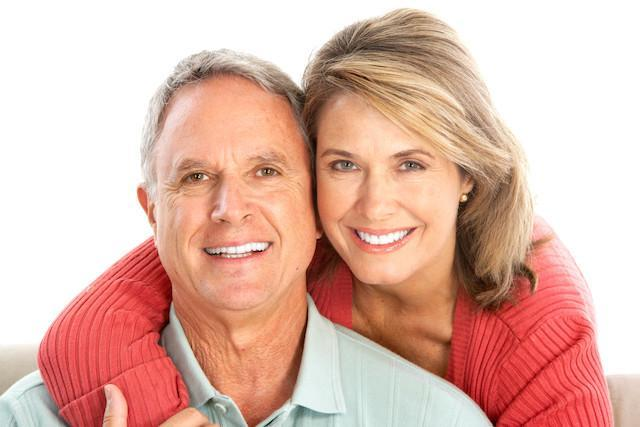 An older couple smiles in front of a white backdrop | Colorado Springs periodontal treatment
