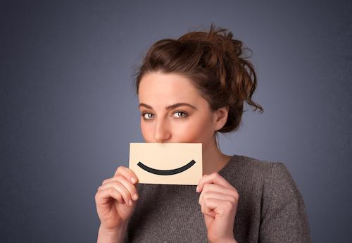 woman holding a picture of a smile over her mouth