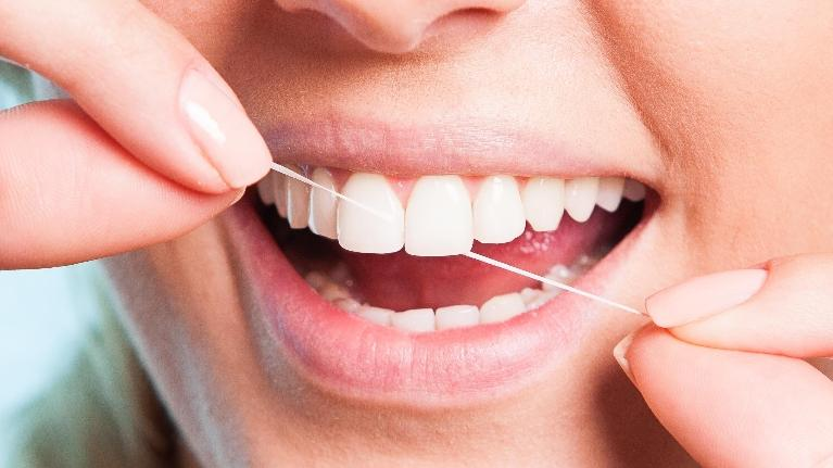An image of a woman flossing | Dentist in Colorado Springs