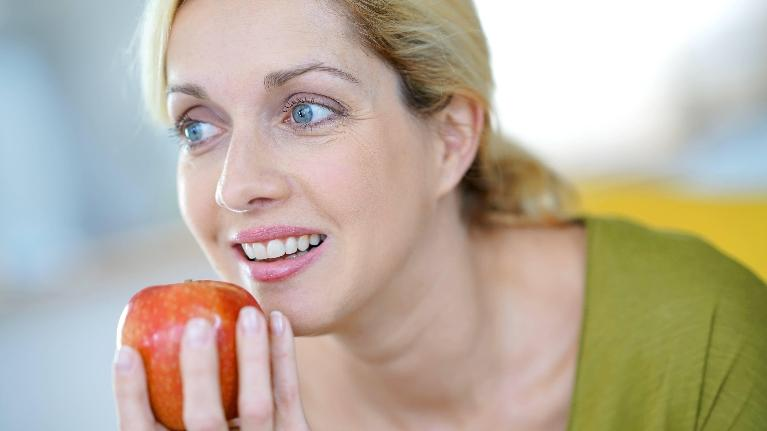 a woman considers taking a bite of an apple | dental extractions colorado springs